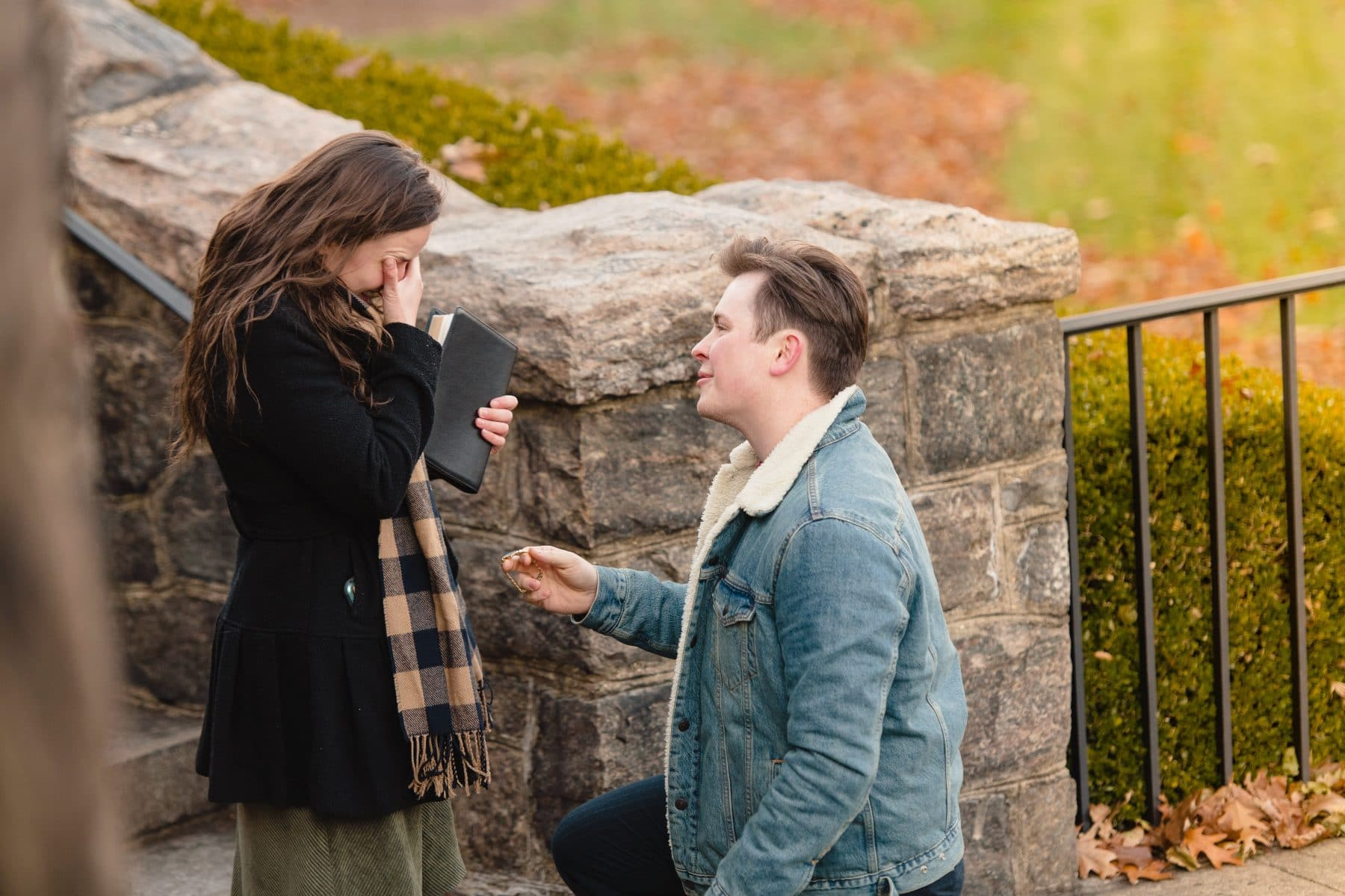 The girlfriend is crying when the boyfriend is on his knee proposing during Bronx Botanical Garden Surprise Proposal