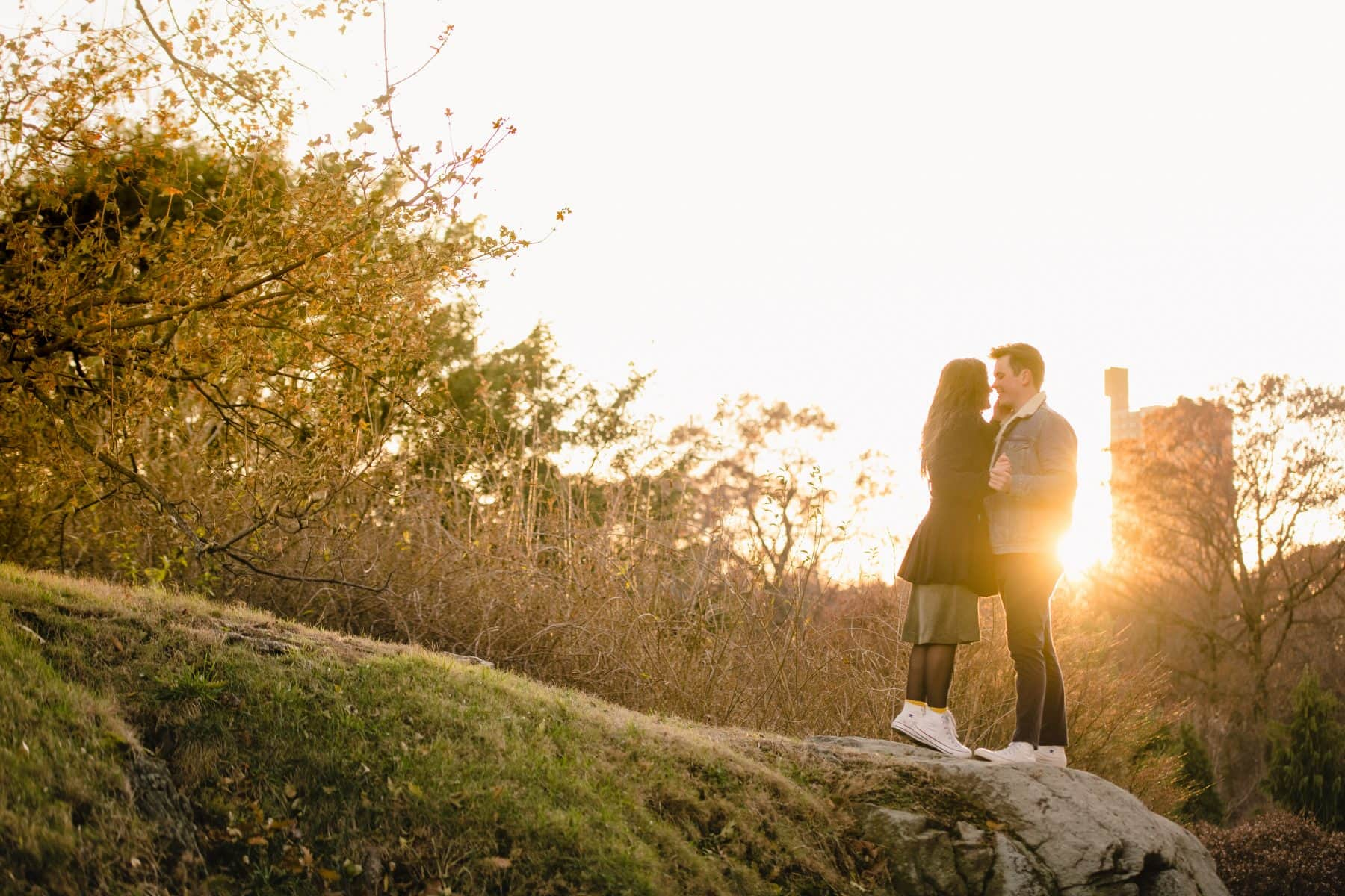 Engaged couple in love standing during sunset on the stone at Bronx Botanical Garden