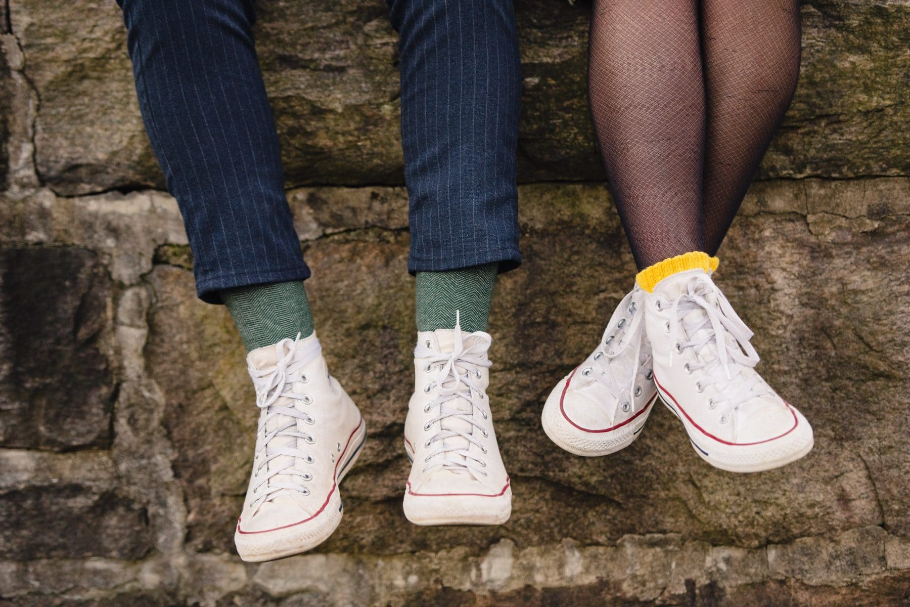 Couples' legs with white snickers and funny socks