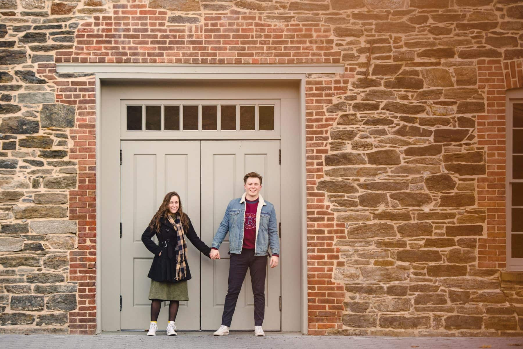 Happy couple in love holding hands against the building wall