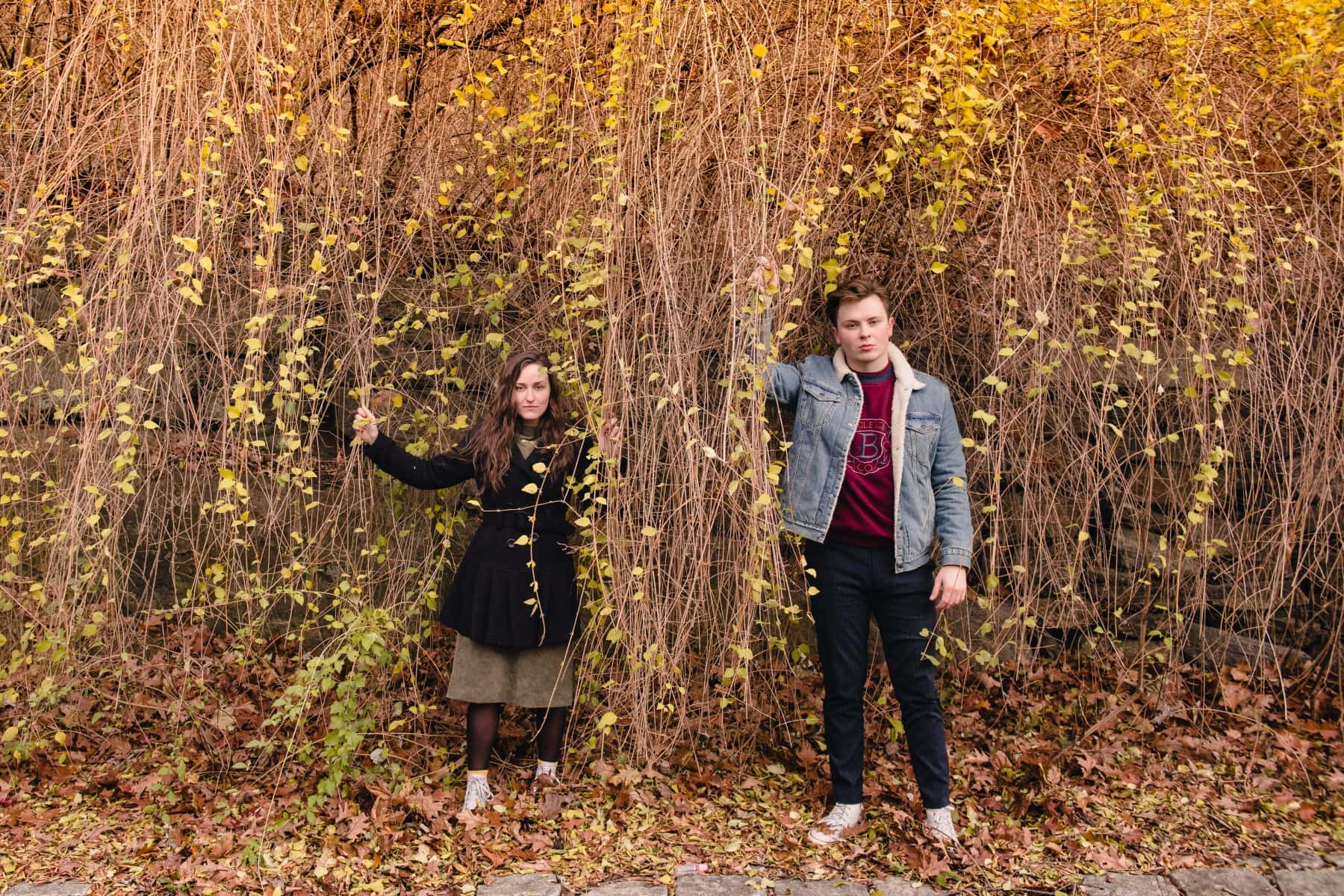 Young couple standing separately and holding tree branches during New York Candid engagement session